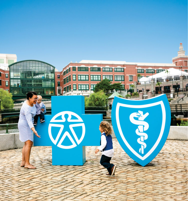 Woman with children in front of BCBSRI logos