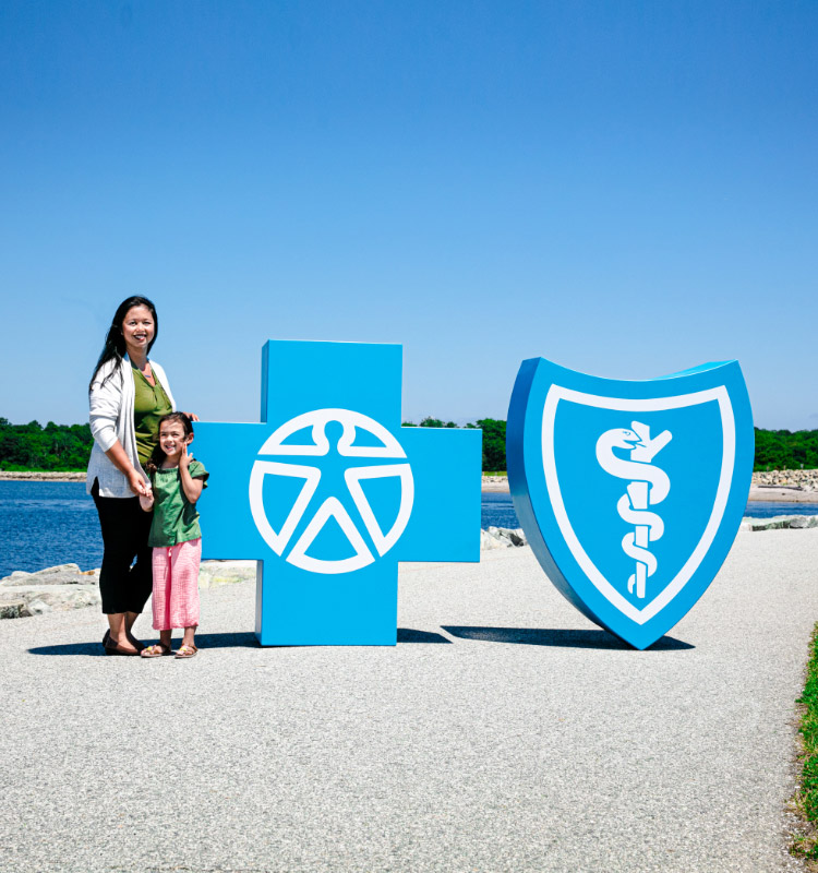 Mother and daughter on beach with BCBSRI logos